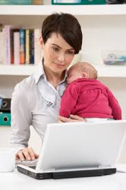 Image of new mom working on laptop with infant in arms