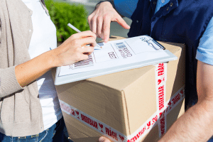 woman signing paper after recieving package