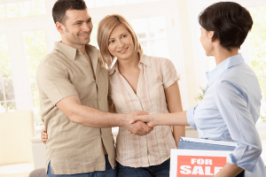Estate agent congratulating young couple on making deal on new house