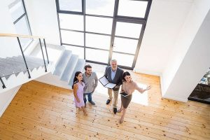 Real estate agent showing new house to couple with digital tablet