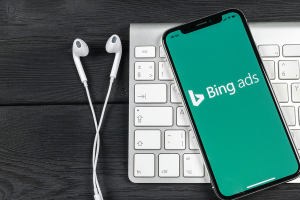 cellphone with Bing Ads on screen, headset and keyboard