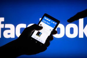 Holding a Smartphone with Facebook app on
