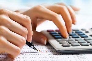 Hand of woman working using calculator