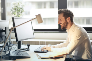 man infront of computer smiling