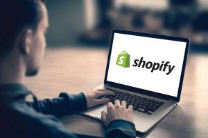 man using laptop, shopify on laptop screen