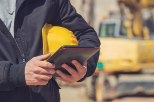 man using ipad with hardhat under arm
