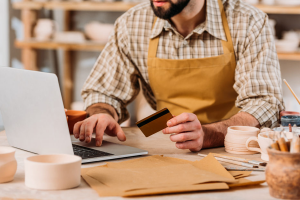 man with apron holding credit card and using laptop