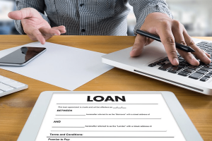 person using laptop behind loan form on table