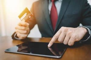 businessman holding a credit card while using tablet
