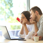 Sad couple looking at their laptop with a credit card