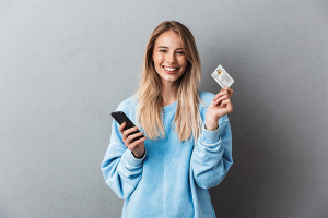 a smiling young lady holding phone and a card