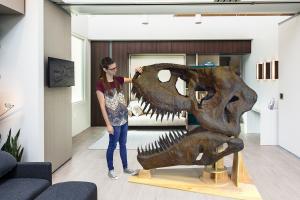 a girl holding dinosaur head