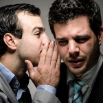 One person whispering to another person in order to influence them