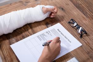 injured man filling work injury claim form