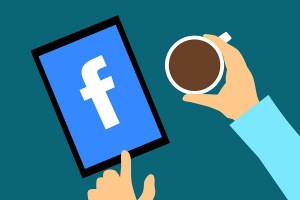facebook app on phone screen and hand holding coffee