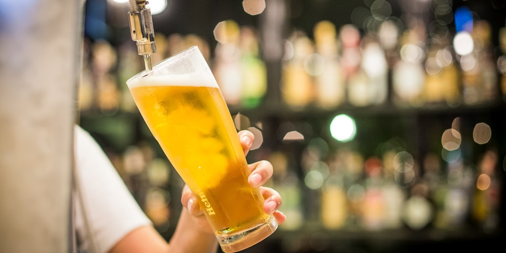 a bartender pouring a local draft beer
