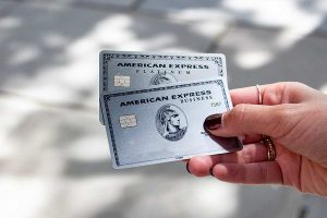A hand holding Two American Express Business Card