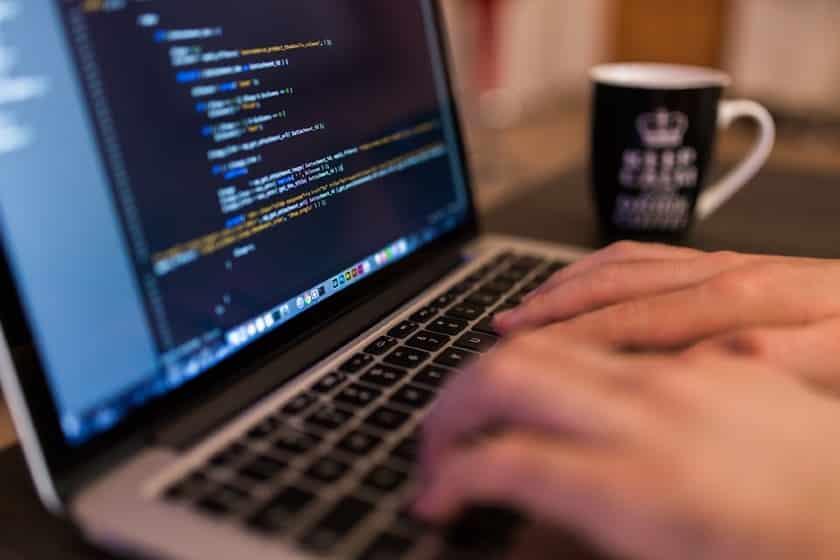 man typing in laptop