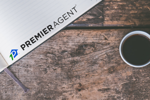 Premier Agent logo on notebook and a coffee