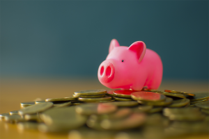 pink piggy bank on top of coins