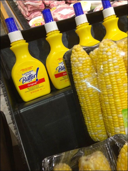 a display that is selling a spray butter product next to ears of fresh corn