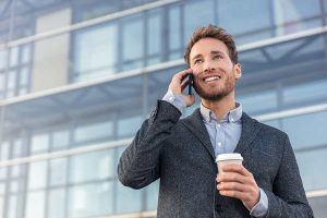 man holding a disposable cup while having a call
