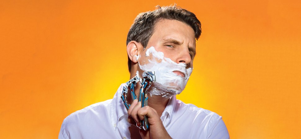 Man holding several razors in Dollar Shave Club advertisement