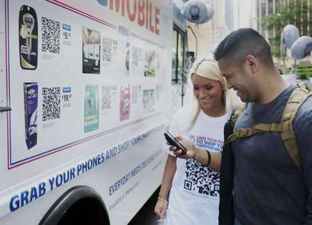 Two people outside a Walmart and Proctor and Gamble mobile phone truck pop-up shop