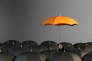 hand holding a yellow umbrella on top of black umbrellas