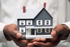hand holding a mini house