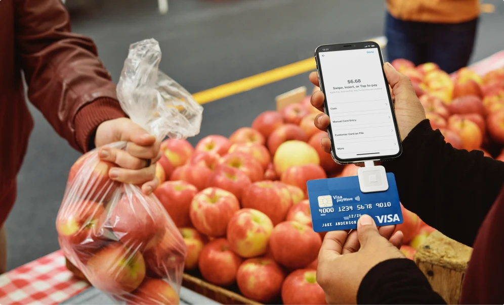 Image of a phone and Square's credit card reader attached to it