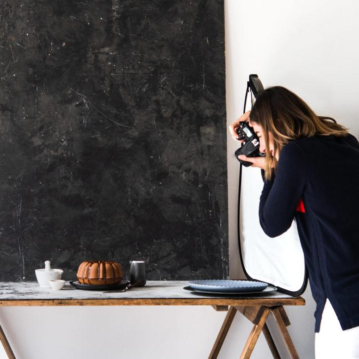 Food photographer taking a photo of a cake
