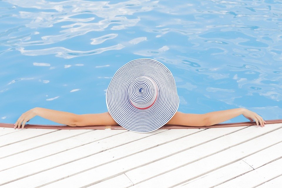 a photo of a woman in a sunhat lounging in a pool