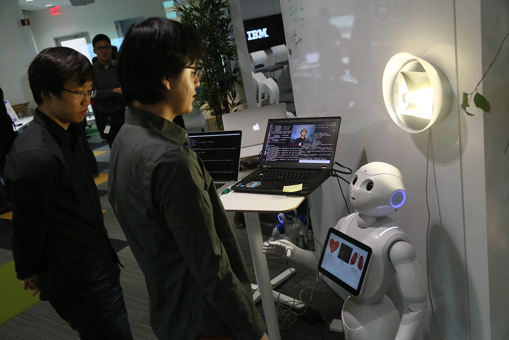 two office employees interacting with an AI powered robotic assistant
