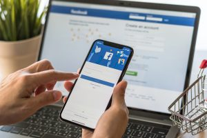 laptop and phone with facebook app