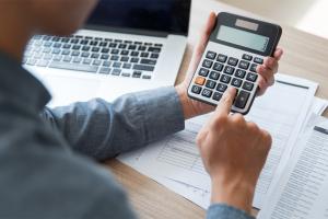 man doing calculations on calculator