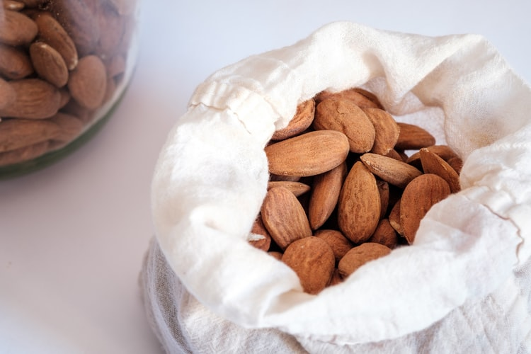 a cloth bag of almonds on a white tabletop