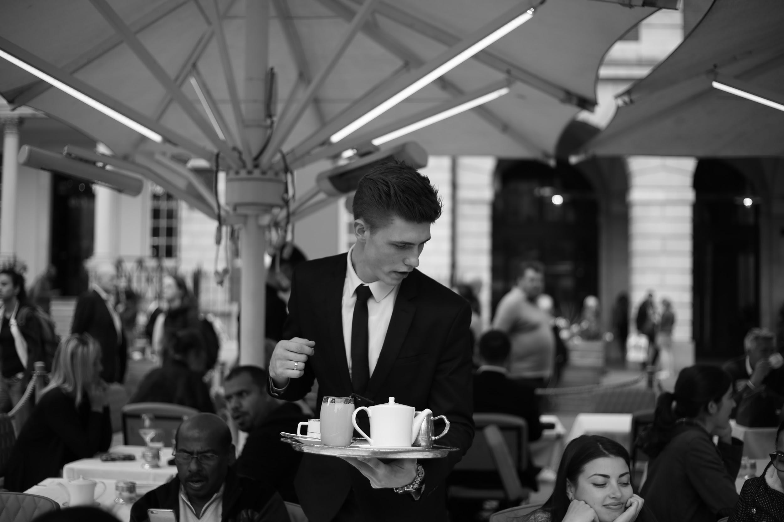 A waiter carrying coffee in a black and white image