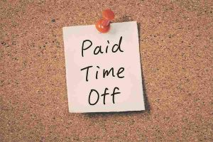 Paid Time Off note pinned to wall