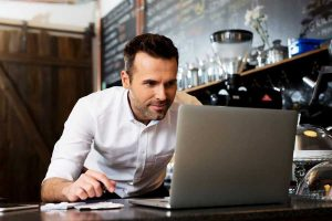 Man enthusiastically working on his laptop