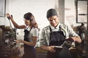Two baristas working together