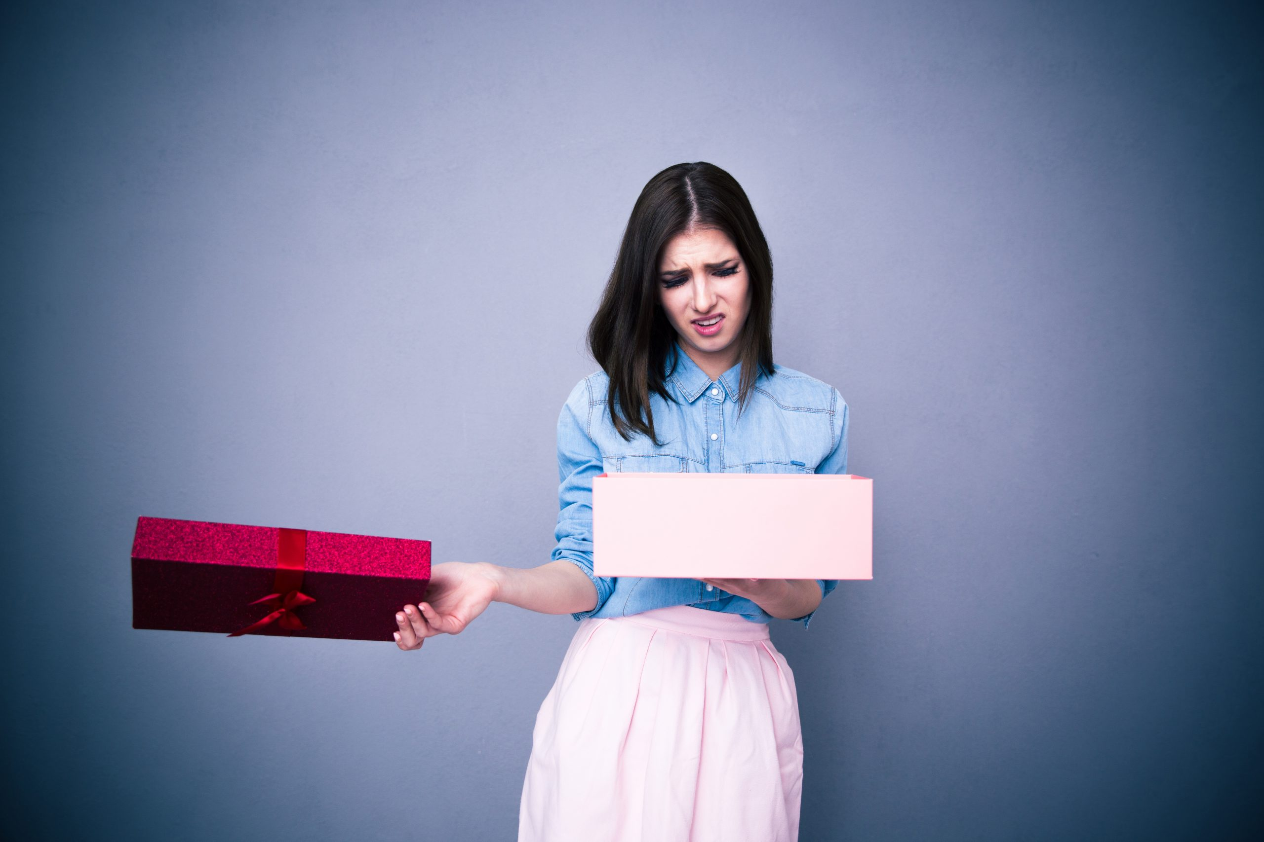 dissatisfied woman opening a gift
