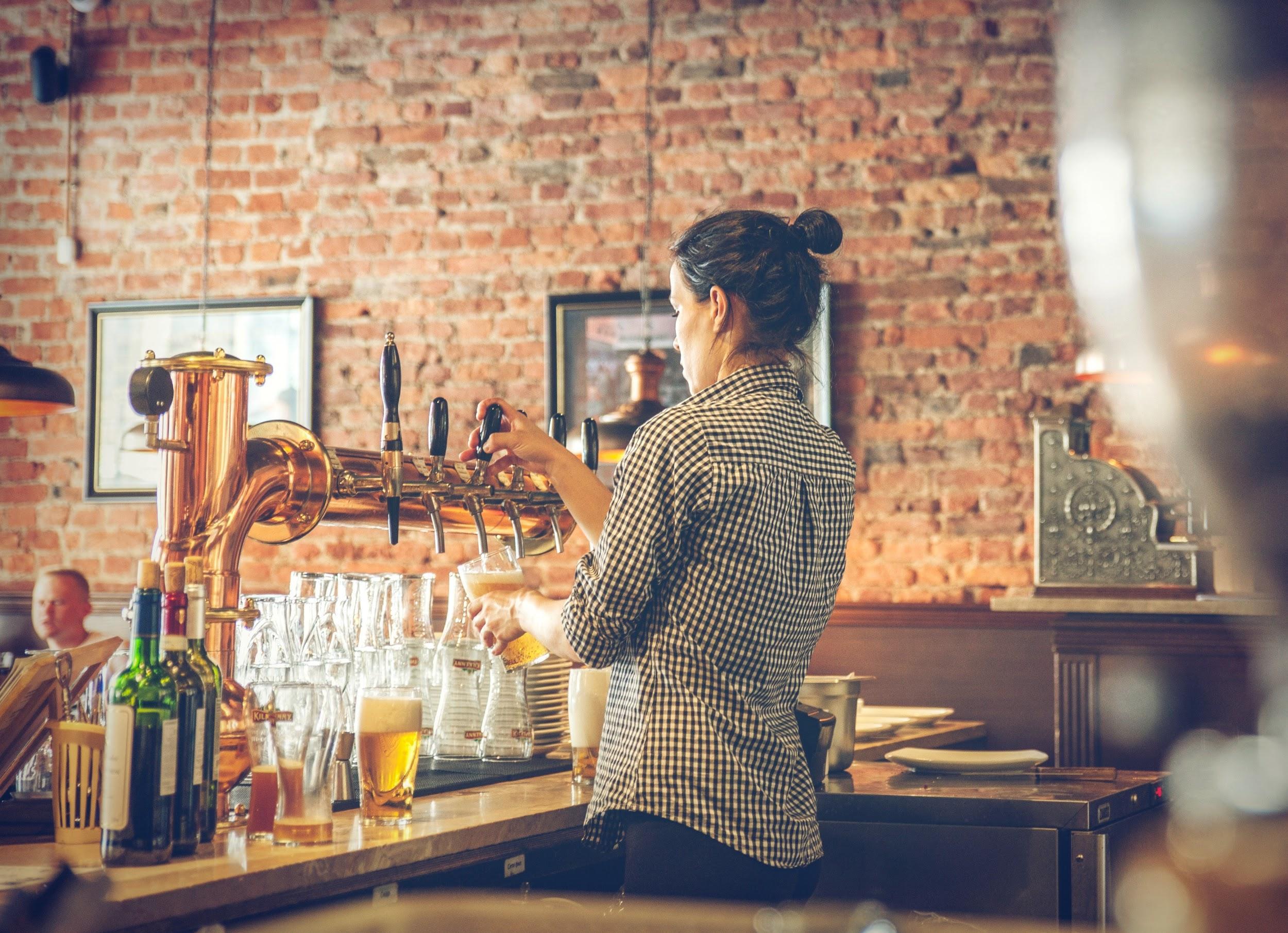A lady bartender filling up some beer