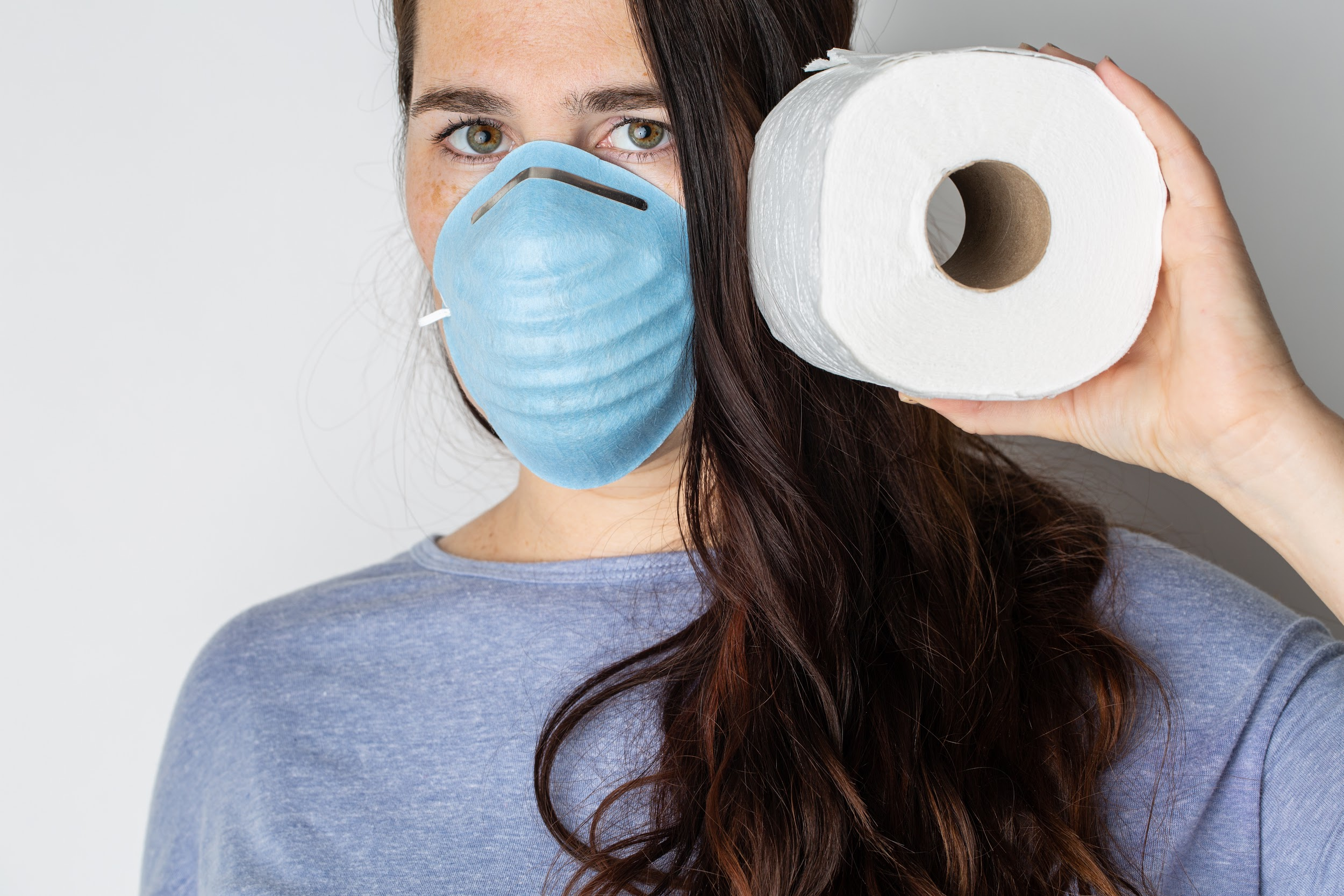 woman wearing a facemask and holding a roll of toilet paper