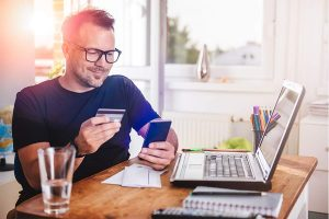 man looking his own credit card and mobile phone