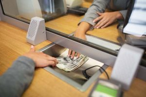 clerk giving cash money to customer at bank office or currency exchanger