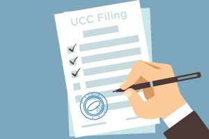 hand checking UCC Filing document