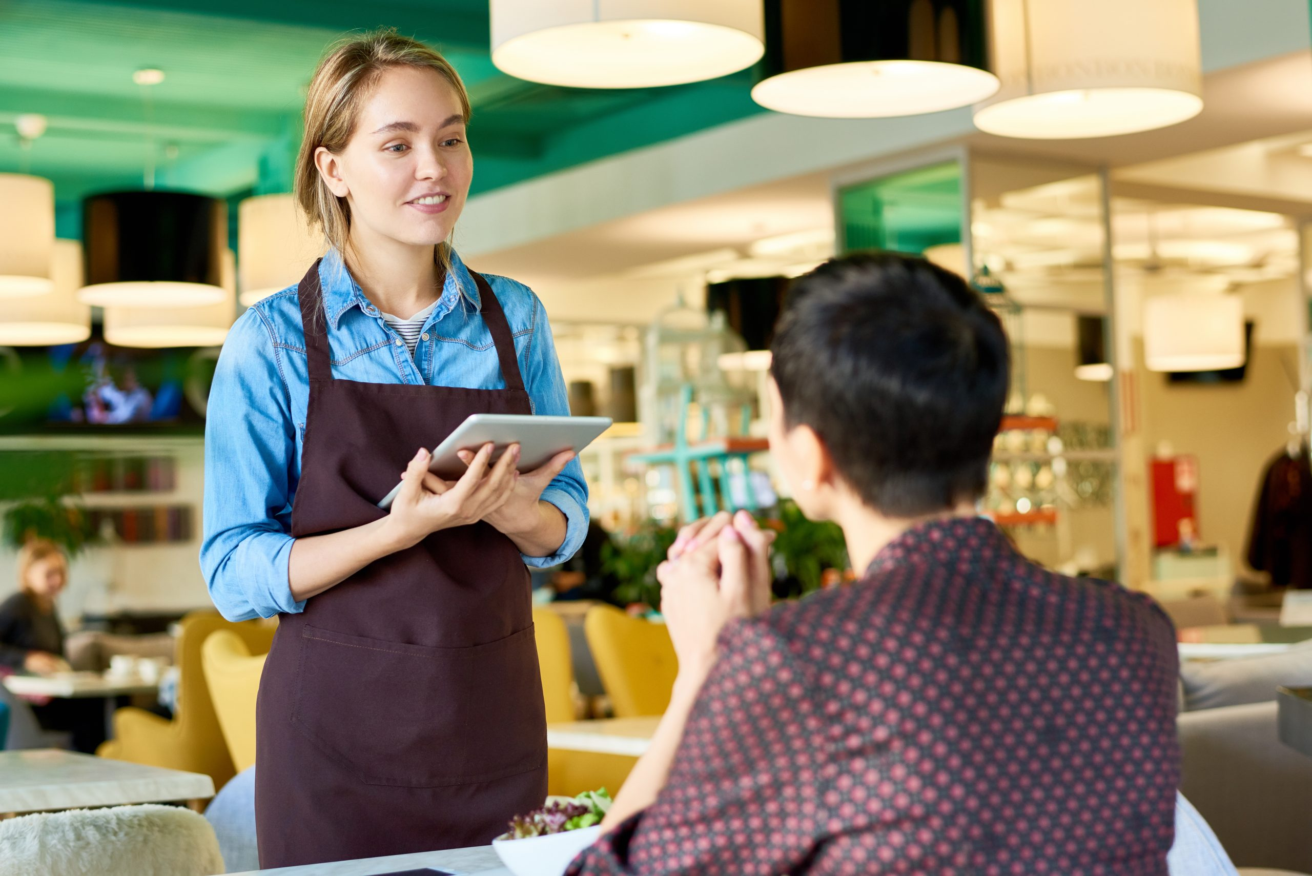 waitress taking order from client in cafe using digital tablet