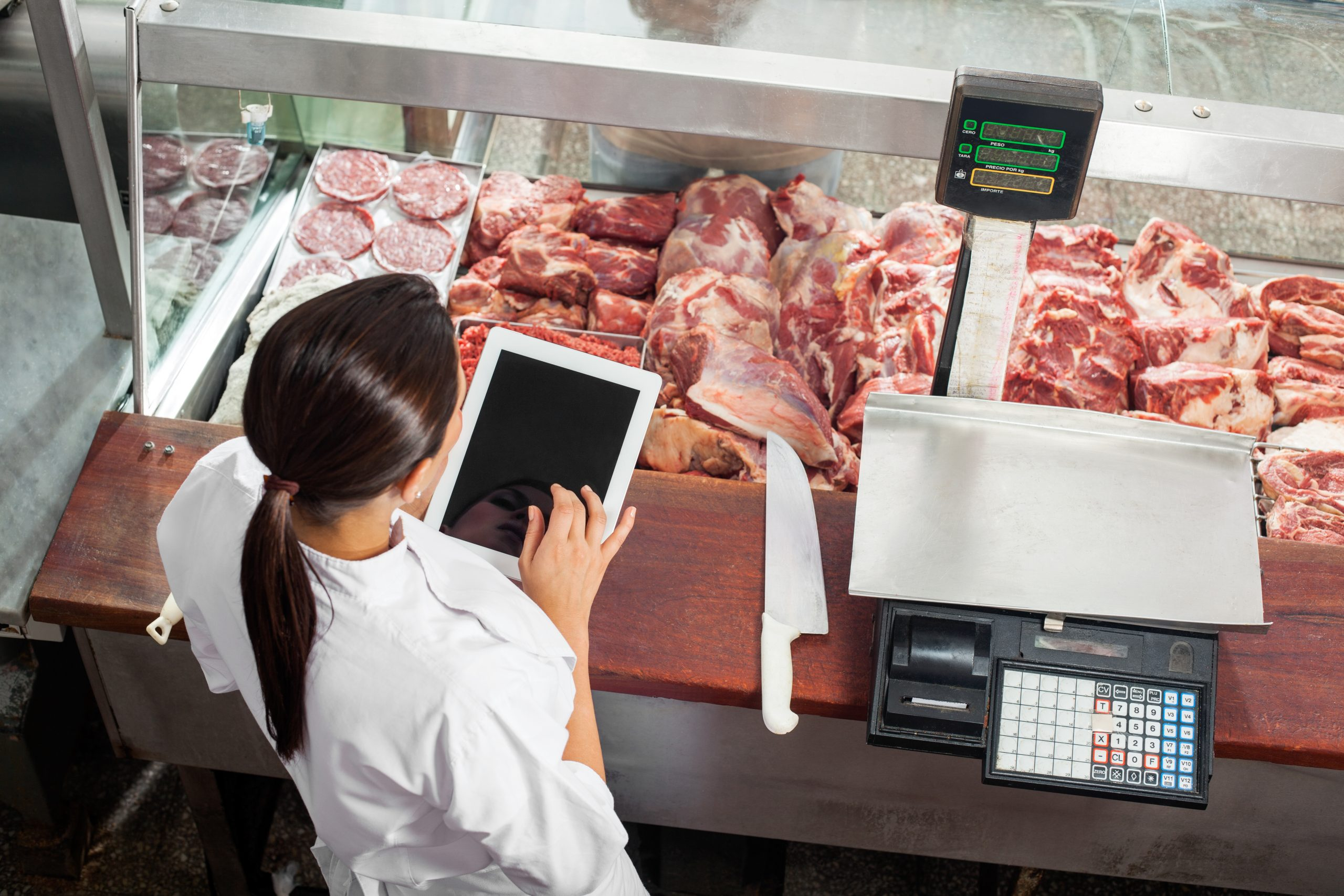 female butcher using digital tablet