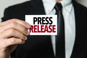 man holding a note with text press release